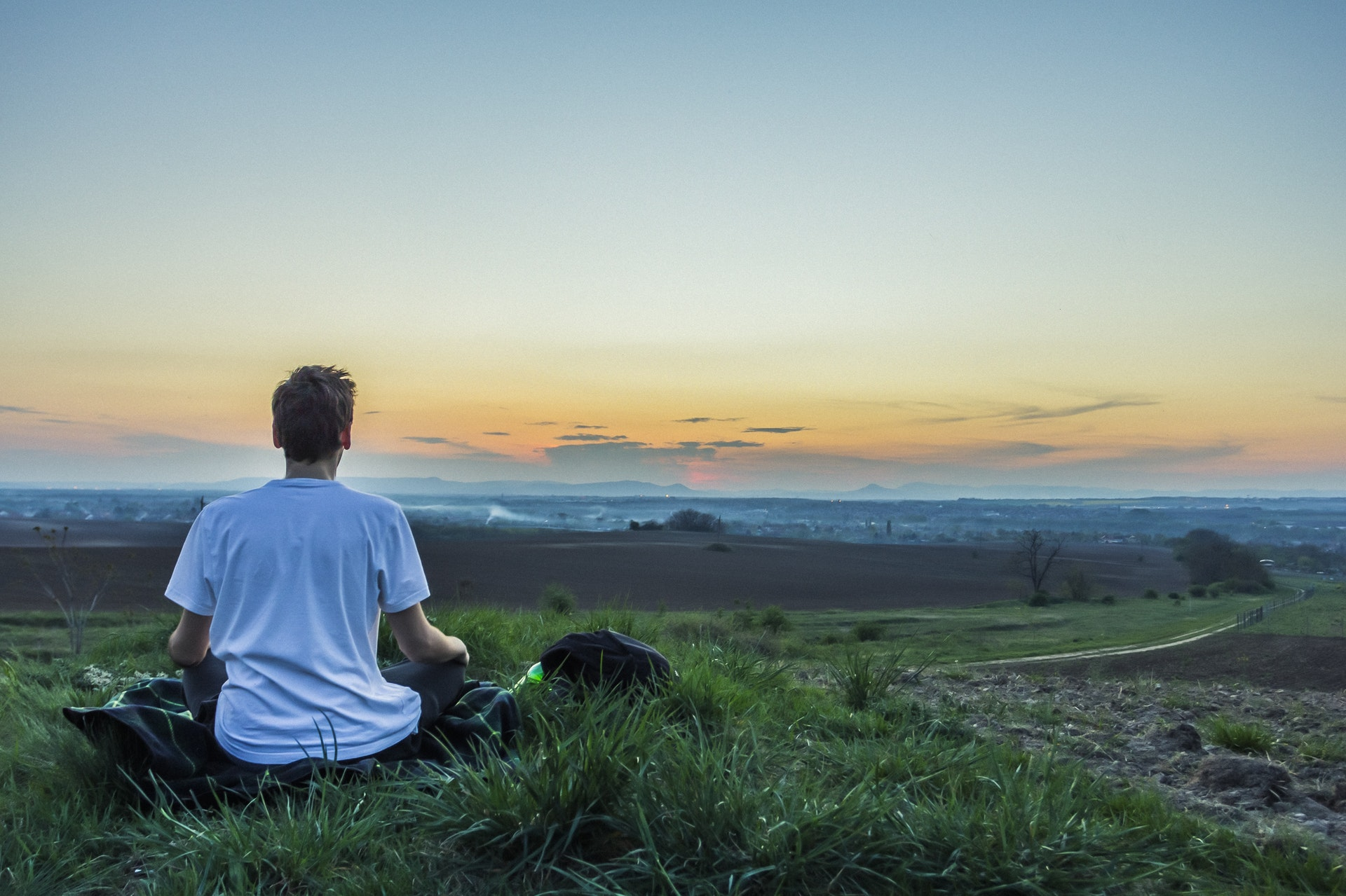 person meditating with beautiful scenery in background